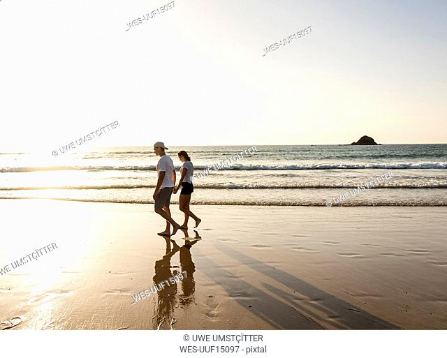 Young couple doing a romantic beach stroll at sunset