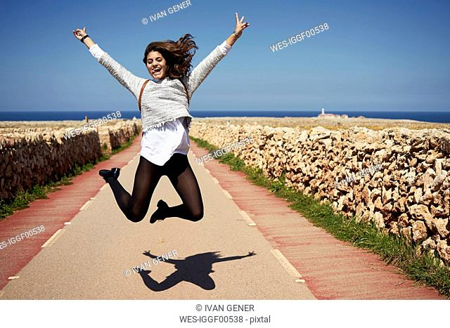 Cheerful young woman jumping in air with rising hands, outdoors