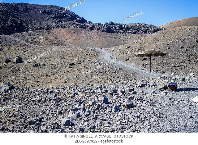 Gravel and volcanic rock path with an umbrella on the Cyclades island to go visit the volcano, in Santorini, Greece. The water is clear, blue and green