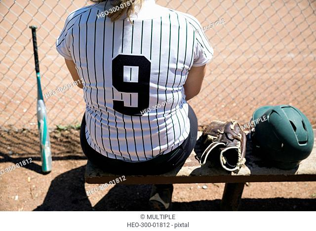Middle school girl softball player sitting on bench next to baseball glove and helmet