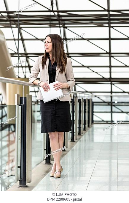Mature business woman standing in an atrium of an office building and holding a tablet; Edmonton, Alberta, Canada