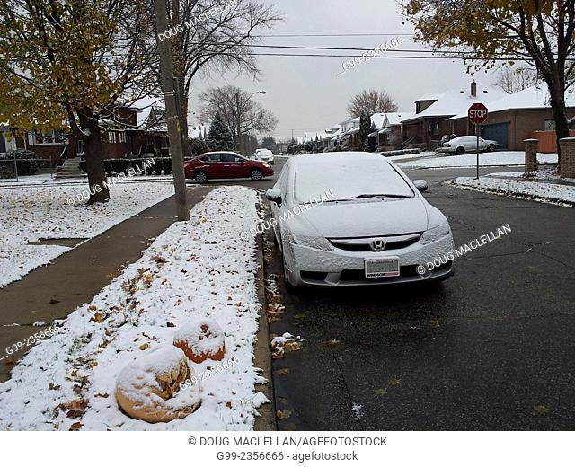 Cars on a residential street during the first snow fall of the season, Windsor, Ontario, Canada
