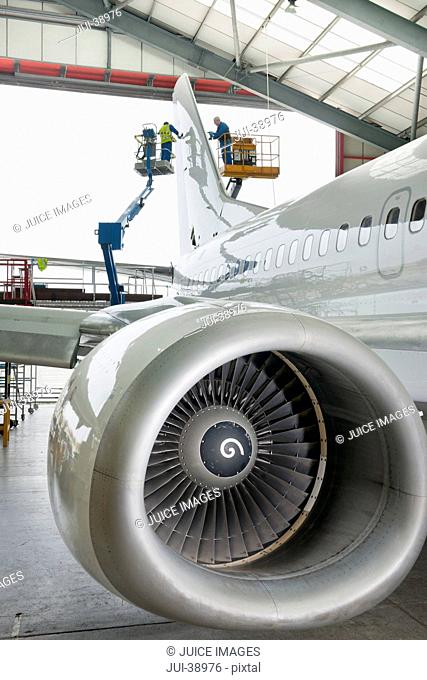 Engineers on hydraulic lifts inspecting tail of passenger jet in hangar