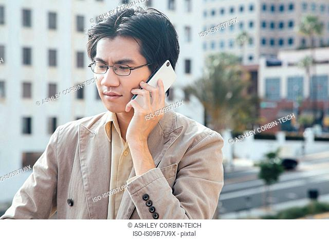 Young man outdoors, using smartphone