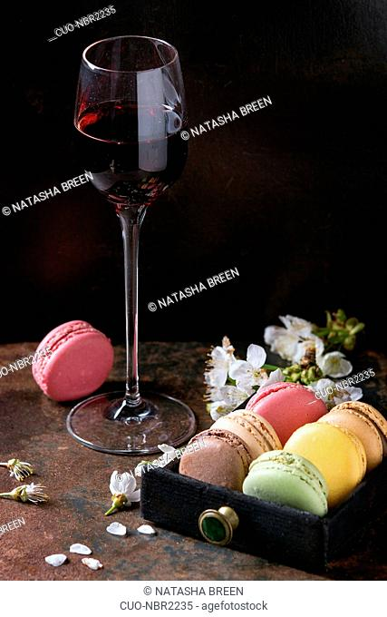 Glass of port wine with variety of colorful french sweet dessert macaron macaroons with different fillings served with spring flowers over dark texture...