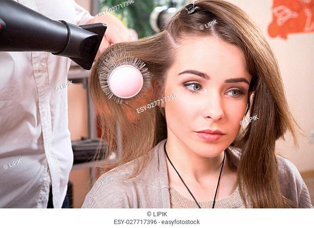 Beautiful lady having her hair dry in hairdressing saloon. Pretty lady looking at mirror while professional hair stylist working