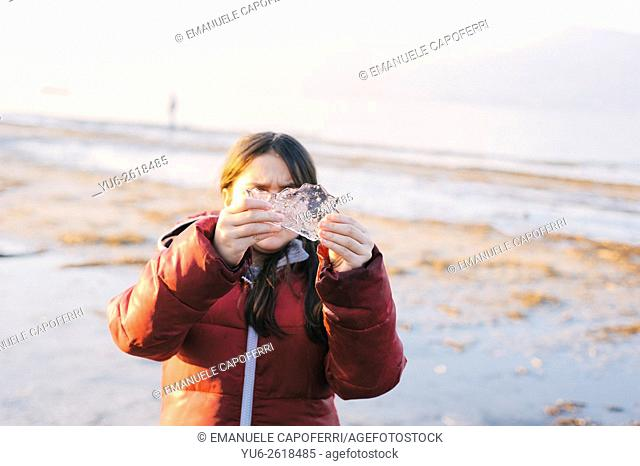 Portrait of little girl in winter beach with a piece of ice in the hands, Ispra, Lake Maggiore, Italy