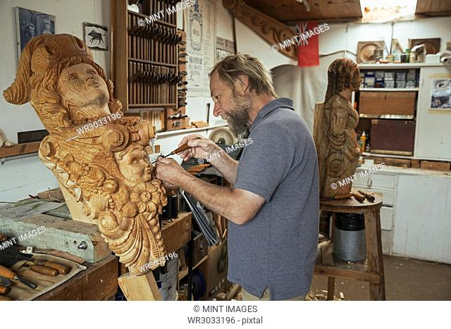 A craftsman, carver working on a wooden female figurehead in a workshop using a fine chisel. A work in progress