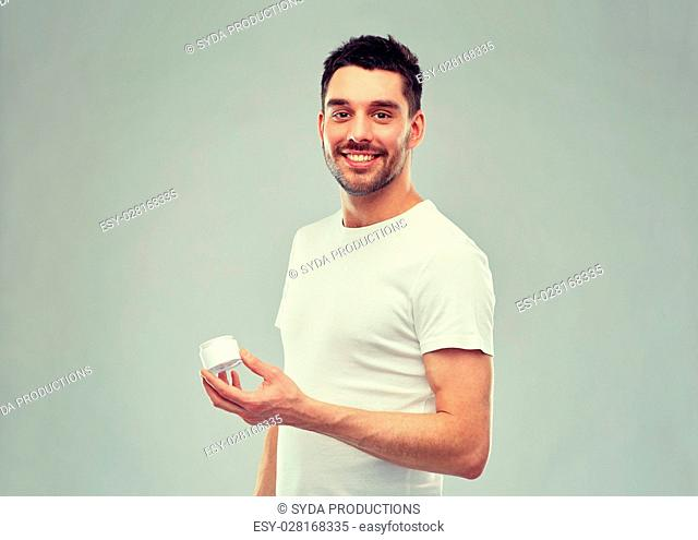 beauty, skin care, body care and people concept - smiling young man with cream jar over gray background