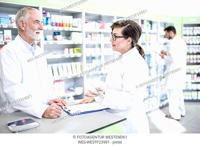 Two pharmacists with clipboard at counter in pharmacy