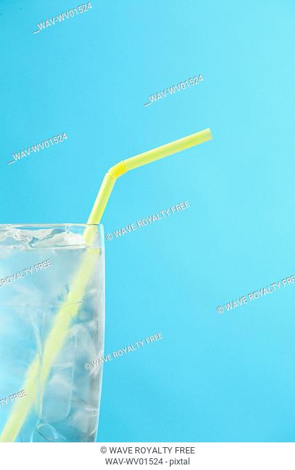 Side portion of clear glass of water with yellow drinking straw