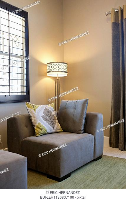 Lit floor lamp by couch in living room; Valencia; California; USA