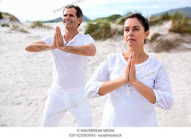Couple performing yoga on beach