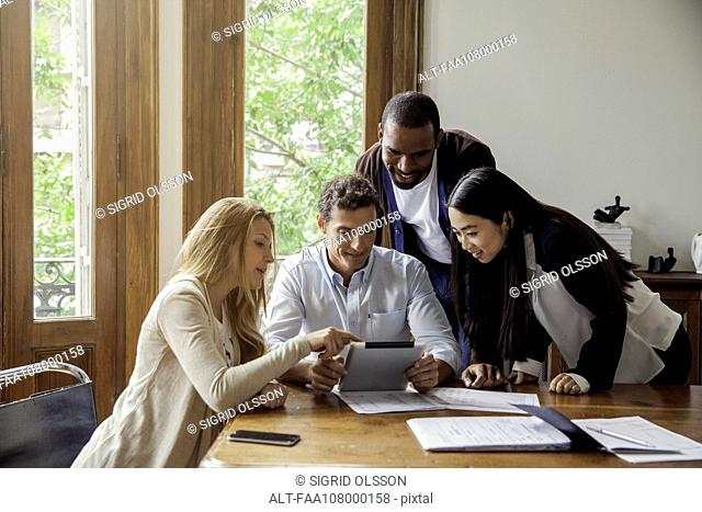 Colleagues looking at digital tablet together in office