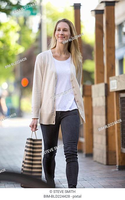 Caucasian woman carrying shopping bag in city