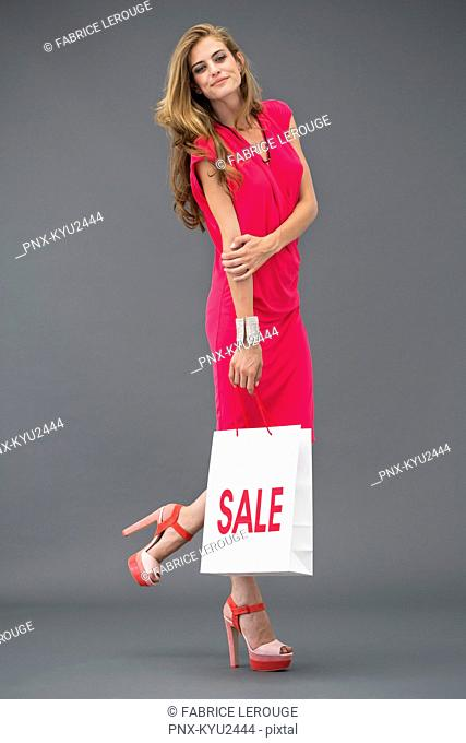 Portrait of a woman posing with a shopping bag