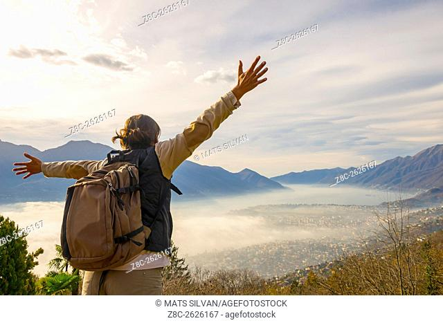 Woman with outstretched arms and backpack enjoy panoramic view with sea of fog over alpine lake Maggiore with mountain in Ticino, Switzerland