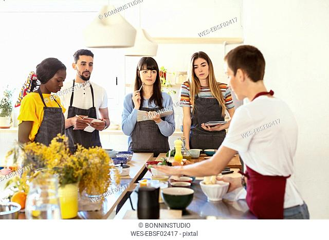 Friends in a cooking workshop listening to instructor