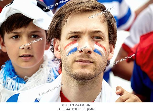 Father and son watching anxiously at French football match