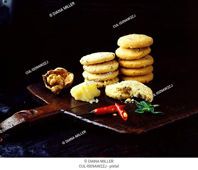 Stacks of homemade walnut chilli cheese oatcakes on vintage wooden tray