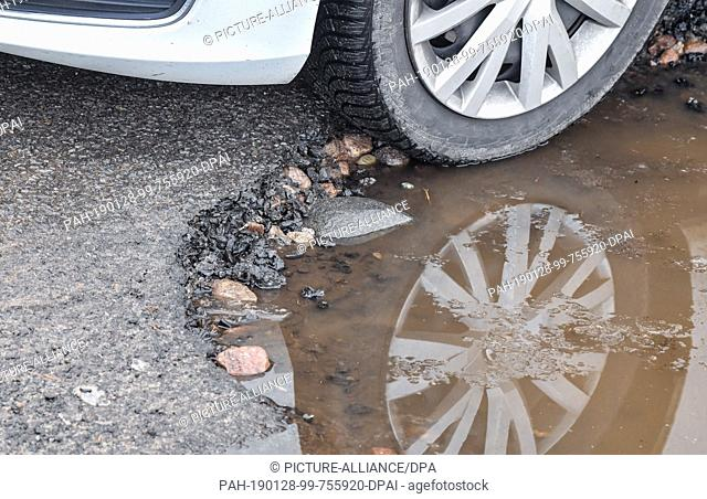 28 January 2019, Brandenburg, Briesen: The car tyre of a Volkswagen is reflected in a puddle on a defective asphalt surface