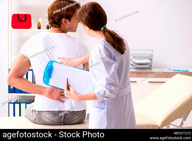 Male patient visiting young female doctor chiropractor