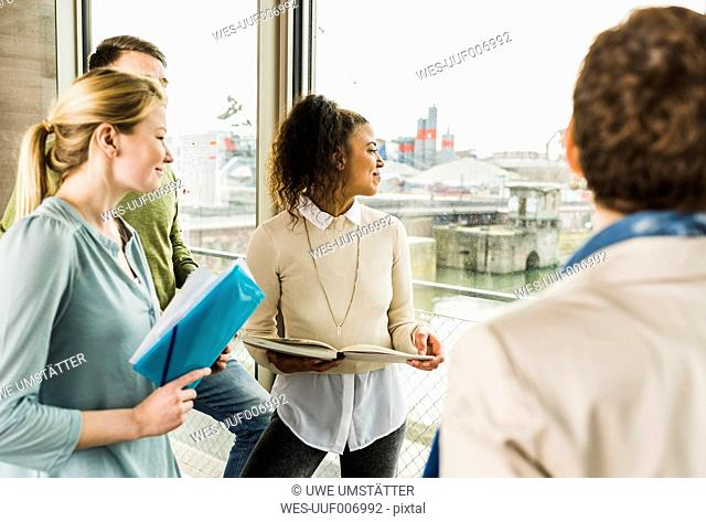 Smiling colleagues in office looking out of window