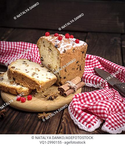 bread cake with raisins and dried fruit is sliced on brown wooden table