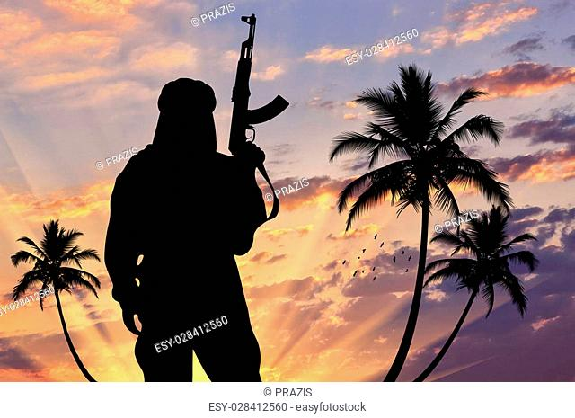 Concept of terrorism. Silhouette of a terrorist with a weapon against a background of a sunset with palm trees
