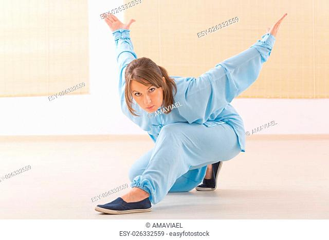 Beautiful woman doing qi gong tai chi exercise wearing professional, original Chinese clothes at gym