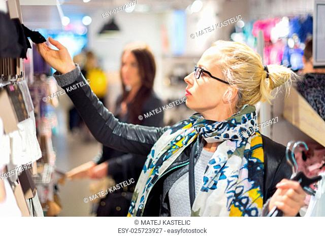 Woman shopping clothes. Shopper looking at clothing indoors in store. Beautiful blonde caucasian female model wearing black glasses