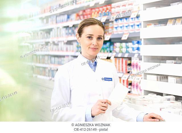 Portrait of confident pharmacist holding prescription in pharmacy