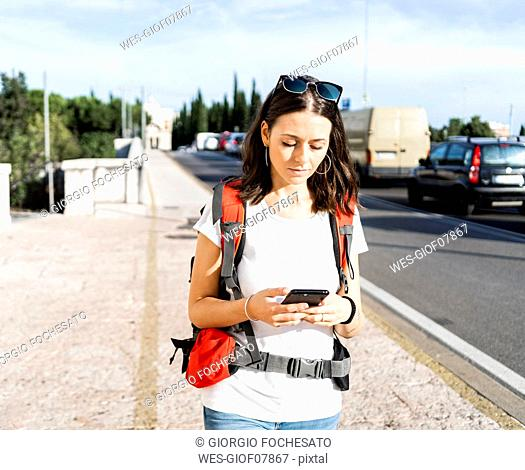 Young female backpacker with red backpack using smartphone in the city, Verona, Italy
