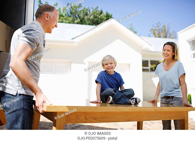 Parents and son moving table from moving van into house