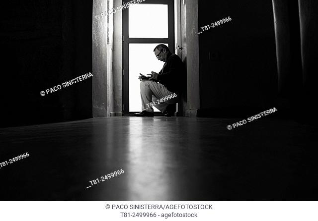 Troubled man looking at a mobile phone