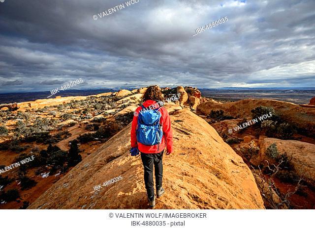 Tourist, young woman hiking on sandstone cliffs, Devil's Garden Trail, Arches National Park, Utah, USA