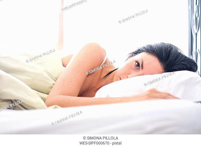 Woman lying on bed, waking up