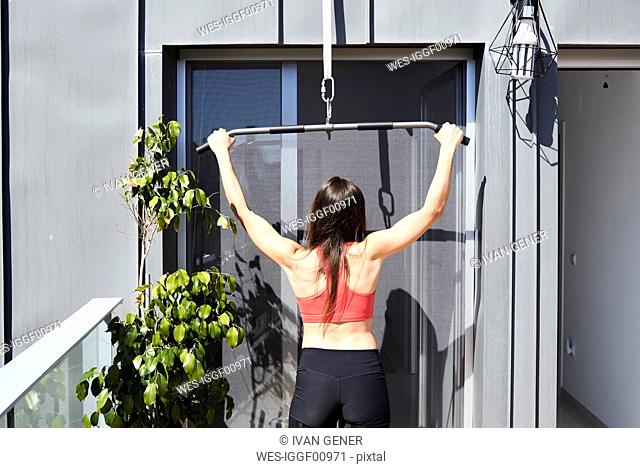 Rear view of sporty young woman exercising on roof terrace