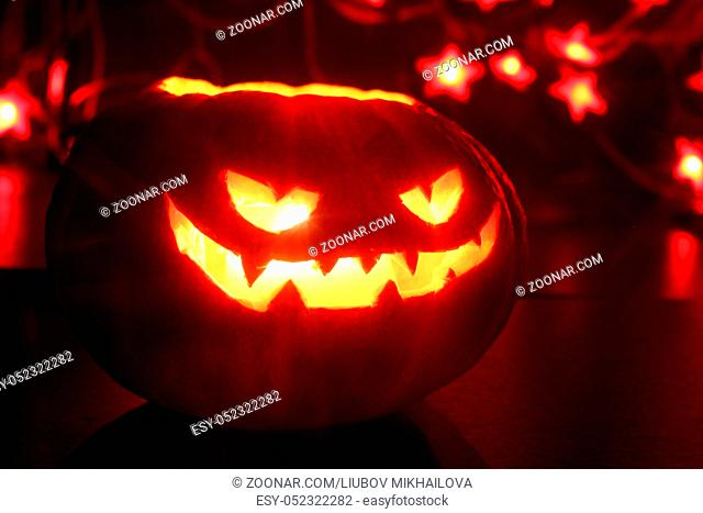 Illuminated cute halloween pumpkin and red bokeh lights on black background