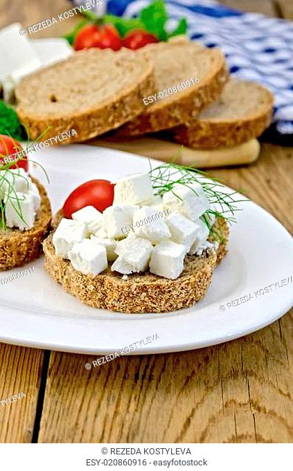 Bread with feta cheese and tomatoes on the board