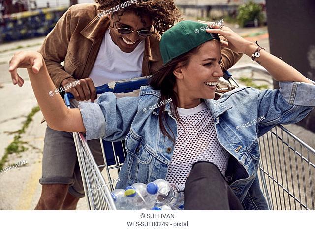 Young man pushing girlfriend sitting in shopping cart