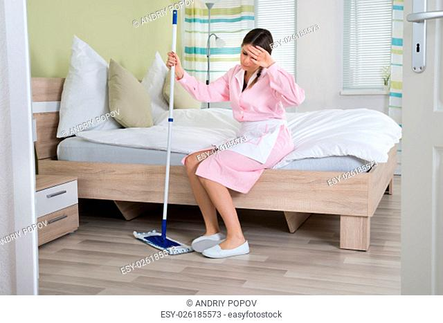 Tired Female Housekeeper Sitting On Bed With Mop In Room