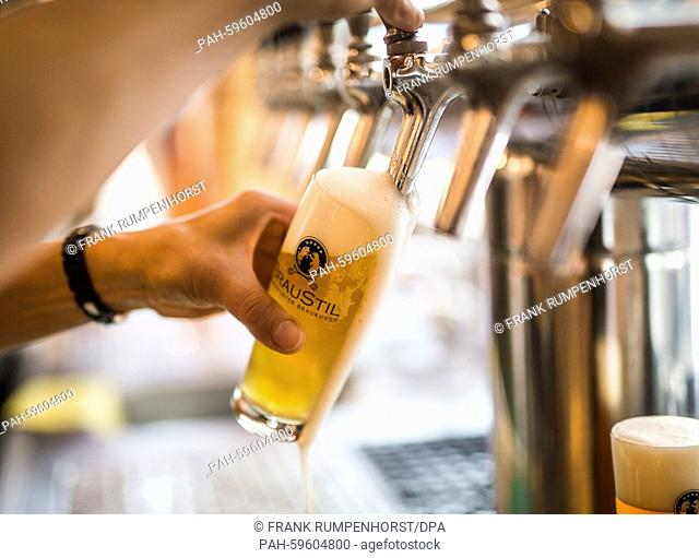 A glass of craft beer is poured in the small brewery 'Braustil,' located in a former gas station in Frankfurt am Main,Germany, 27 June 2015