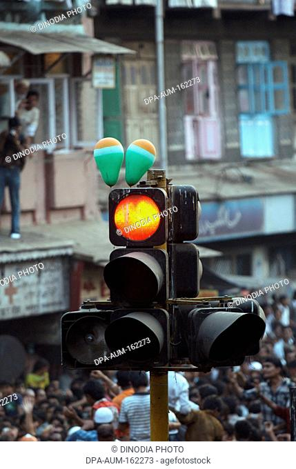 Balloons tied on signal showing red light at traffic junction in Bombay Mumbai ; Maharashtra ; India