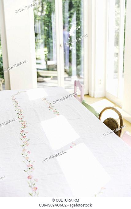 Sunlight on dining room table with white table cloth