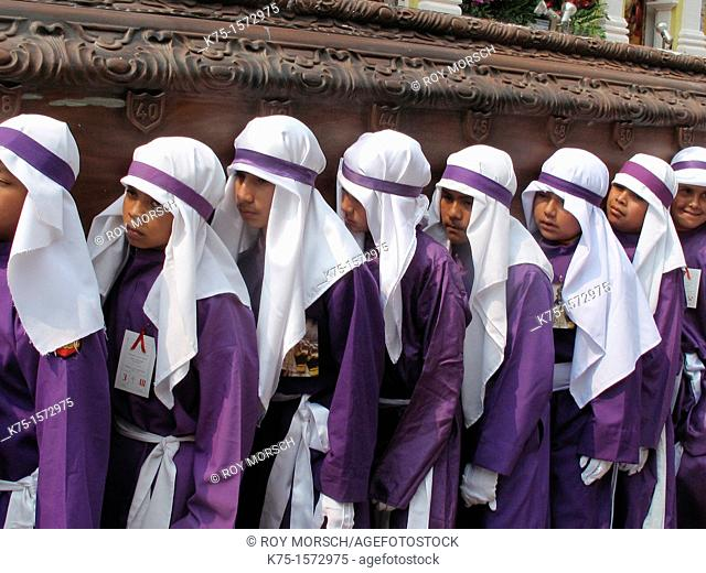 Purple robed boys carrying heavy float during Holy Week