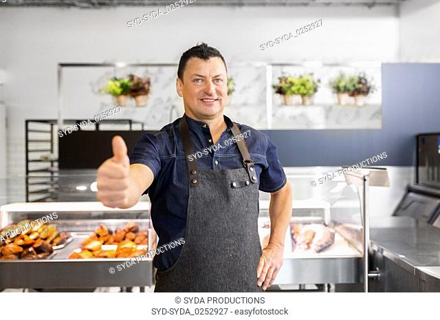 seafood seller at fish shop showing thumbs up