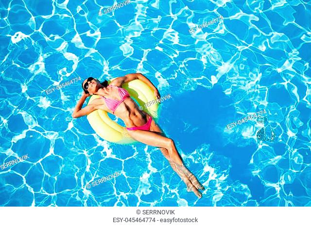 Attractive sexy woman in pink bikini relaxing on yellow rubber ring in the swimming pool in summer