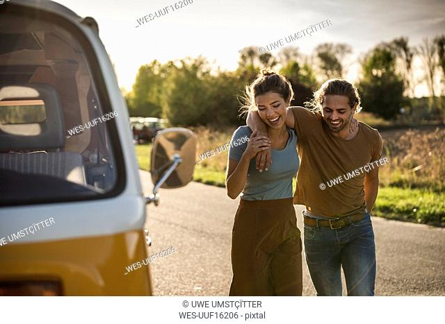 Affectionate couple walking on the road with arms around, next to their camper
