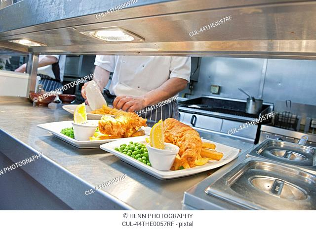 Chef with plates of food in kitchen